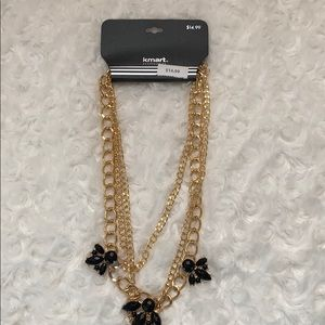 Gold necklace with a black flowers